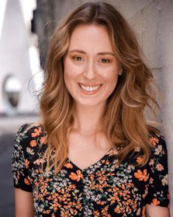 Headshot of a woman with a floral shirt leaning against a wall and smiling at the camera